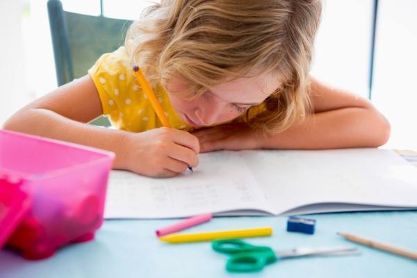 κοριτσάκι γράφει τα μαθήματα του