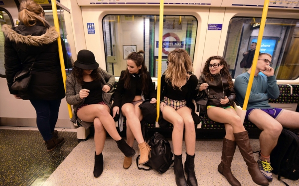 "Participants in the annual International ""No Pants Subway Ride"" travel on a London underground train in London, on January 10, 2016. Started in 2002 with only seven participants, the day is now marked in over 60 cities around the world. The idea behind ""No Pants"" is that random passengers board a subway car at separate stops in the middle of winter, without wearing trousers. The participants wear all of the usual winter clothing on their top half such as hats, scarves and gloves and do not acknowledge each other's similar state of undress. AFP PHOTO / LEON NEALLEON NEAL/AFP/Getty Images"