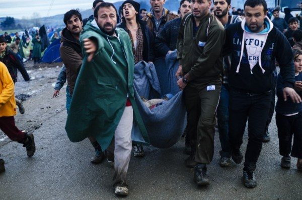 Migrants carry in a blanket a woman injured after a food distribution on March 10, 2016, in a makeshift camp at the Greek-Macedonian border, near the Greek village of Idomeni, where thousands of refugees and migrants are stranded by the Balkan border blockade. The German and Greek leaders blasted Balkan countries for shutting their borders to migrants ahead of an EU ministers meeting on March 10. Greek authorities said there were 41,973 asylum seekers in the country, including some 12,000 stuck at Idomeni on the closed Macedonian border. / AFP / DIMITAR DILKOFF
