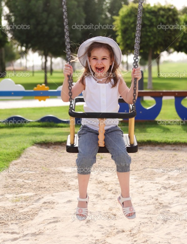 Laughing little girl on swing in summer park